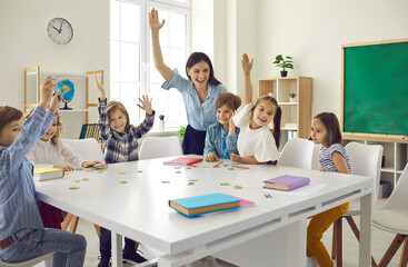 Happy clever enthusiastic school children and teacher raising hands. Confident preschoolers or first grade students sitting around big classroom table, learning letters, reading books and having fun