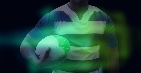 Composition of glowing green blur over male rugby player holding rugby ball, on black