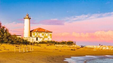 Lighthouse On Beach By Buildings Against Sky