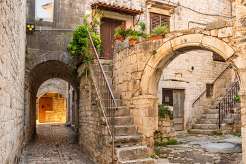 Picturesque street in Trogir city with flower pots and fresh laundry