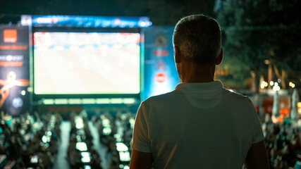 Man watching football in a public place at night