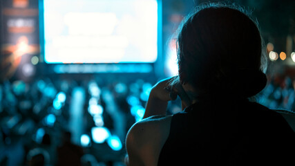 Woman watching football in a public place at night