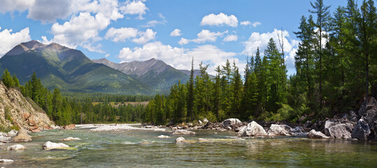 Panoramic view of the Irkut mountain river against the backdrop of the Eastern Sayan Mountains on a sunny summer day. Beautiful summer landscape. Natural background