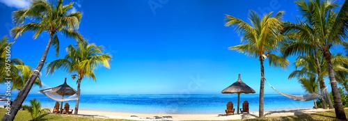 Panorama tropikalnej plaży z krzesłami i parasolami