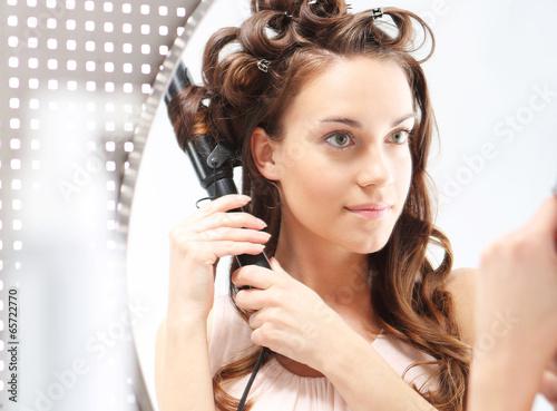 Kobieta nakręca włosy na lokówkę.