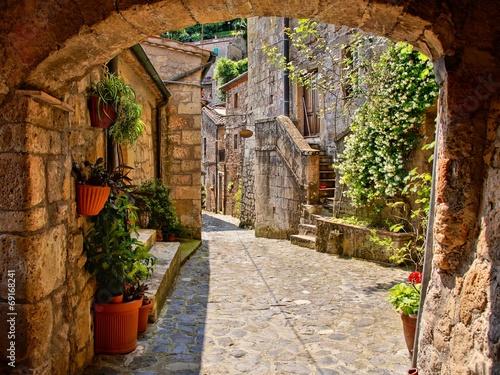 Łukowata brukowiec ulica w Toskańskiej wiosce, Włochy