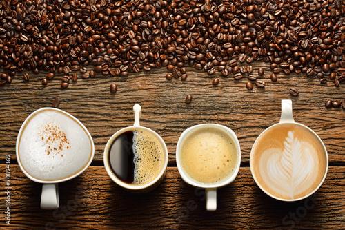 Wybór filiżanek kawy i ziaren kawy na starym drewnianym stole