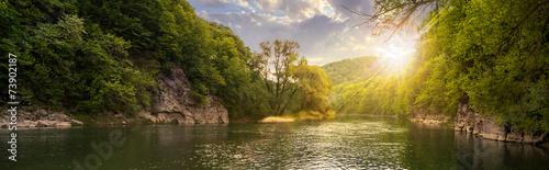 leśna rzeka z kamieniami na brzegach o zachodzie słońca