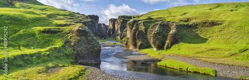 zielone wzgórza kanionu z rzeką i niebem w Islandii