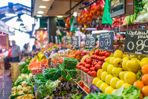 Price tags on market stall. Fruits and vegetables for sale at La Boqueria, a large public market in the Ciutat Vella district of Barcelona