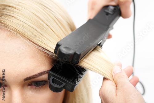 Prostowanie włosów.Fryzjer modeluje fryzurę za pomocą prostownicy