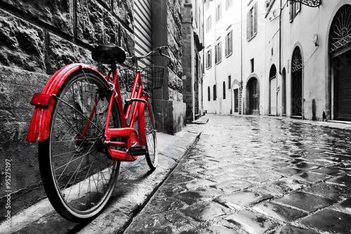 Retro vintage czerwony rower na brukowanej uliczce na starym mieście. Kolor w czerni i bieli