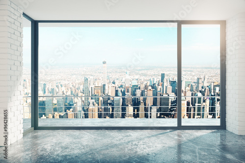 Pusty pokój na poddaszu z dużym oknem w podłodze i widokiem na miasto