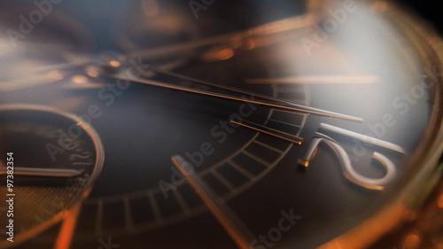 Piękny damski złoty zegarek, strzała wskazuje na godzinę dwunastą, efekt dużej głębi ostrości.