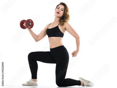 Piękna kobieta brunetka ćwiczy w siłowni