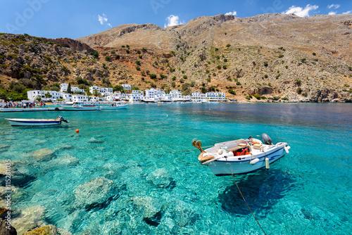 Mały motorboat przy jasną wody zatoką Loutro miasteczko na Crete wyspie, Grecja