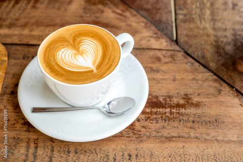 Zamknij się biały kubek kawy z latte art kształcie serca na zakładce drewna