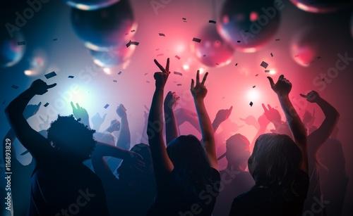 Młodzi szczęśliwi ludzie tańczą w klubie. Koncepcja życia nocnego i dyskoteki.