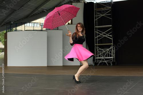 Piękna kobieta tańczy z parasolką na scenie amfiteatru.