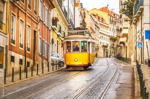 Klasyczny żółty tramwaj na ulicy w Lizbonie, Portugalia