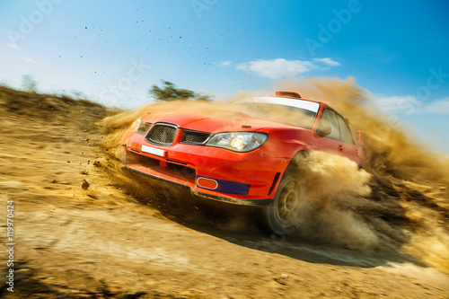 Potężny czerwony samochód rajdowy w drifcie na polnej drodze