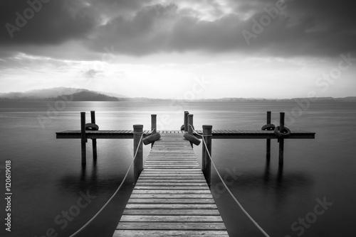 Drewniany molo na jeziornym Zug, Szwajcaria. Długi czas ekspozycji. Czarny i biały.