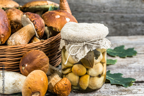 Boletus mushrooms marinated in jar on rustic wooden table