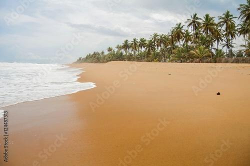 Tropical Azuretti beach on the Atlantic ocean coast in Grand Bassam, stock image. Ivory Coast, Africa. April 2013.
