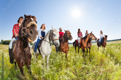 Happy equestrians riding horses in summer meadow