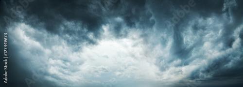 Dramatyczne niebo w tle. Stormy Clouds in Dark Sky. Moody Cloudscape. Obraz panoramiczny może być używany jako baner internetowy lub nagłówek strony. Zdjęcie stonowane i przefiltrowane z miejsca kopiowania.