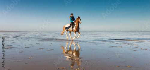 cavalière au galop sur la plage