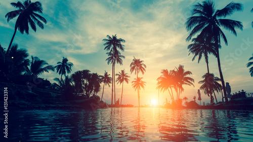 Piękna tropikalna plaża z palmami sylwetki o zmierzchu.