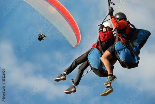 Dwie tandemowe paralotnie latają na tle błękitnego nieba, tandemowe paralotniarstwo prowadzone przez pilota