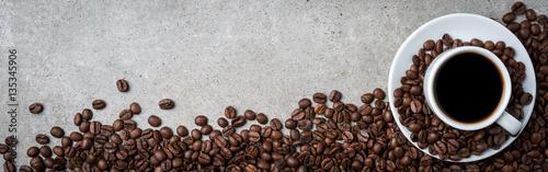 Filiżanka kawy z kawowymi fasolami na popielatym kamiennym tle. Widok z góry