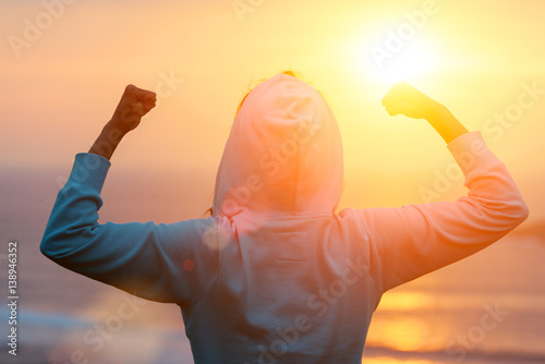 Widok z tyłu silnie zmotywowanej kobiety świętuje cele treningowe w kierunku słońca. Sukces zdrowego treningu rano.