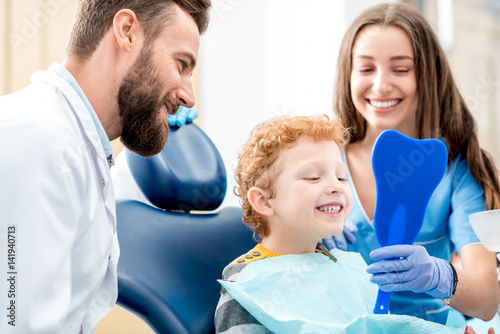 Młoda chłopiec patrzeje lustro z toothy uśmiechu obsiadaniem na krześle z dentystą i asystentem przy stomatologicznym biurem
