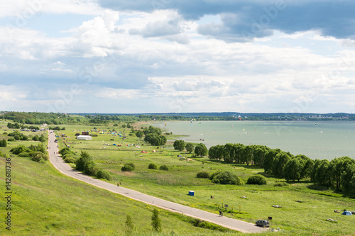 Romantic road into the distance, horizon, lake and green flat plain. Sports and recreation in auto kemping on Plesheevo lake resort.