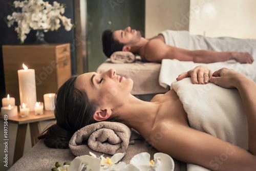 Mężczyzna i kobieta w pozycji leżącej na łóżkach do masażu w azjatyckim centrum odnowy biologicznej