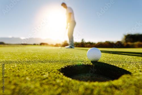 Mężczyzna stawia piłkę na polu golfowym na zielono