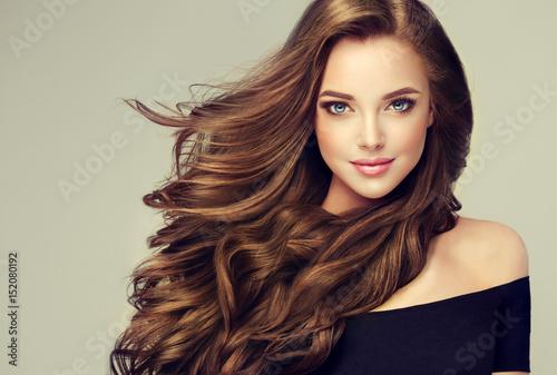 Brunetka dziewczynka z długie i lśniące falowane włosy. Piękny model z kręconą fryzurą.