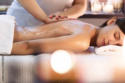 Masaż ciała i zabieg spa w nowoczesnym salonie ze świecami
