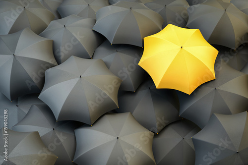 Individuality and difference concept, top view of unique yellow umbrella standing out from the gray crowd