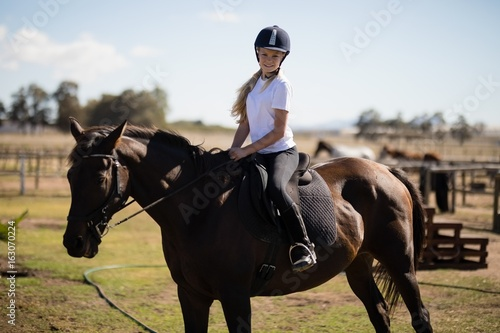 Smiling girl riding a horse in the ranch