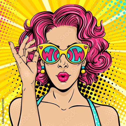 Wow, twarz pop-artu. Seksowna zdziwiona kobieta z różowym kędzierzawym włosy i otwartymi ustami trzyma okulary przeciwsłonecznych w jej ręce z inow wow w odbiciu. Kolorowe tło wektor w retro komiks stylu pop-art.
