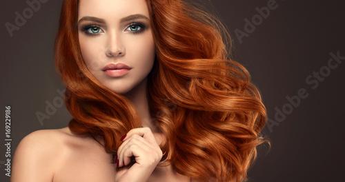Piękna modelka z długimi rudymi kręconymi włosami. Czerwona głowa. Produkty do pielęgnacji, farbowanie włosów.