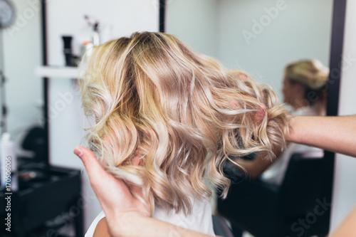 Piękna fryzura młodej kobiety po farbowaniu włosów i wykonywaniu pasemek w salonie fryzjerskim.