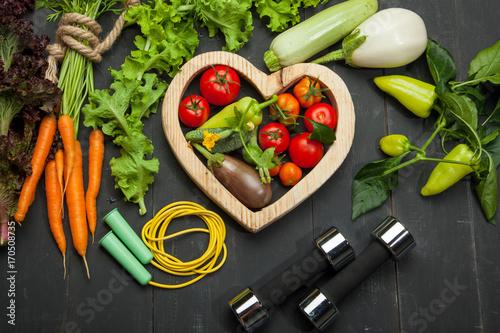 Świezi warzywa, dieta i sport na czarnym drewnianym tle