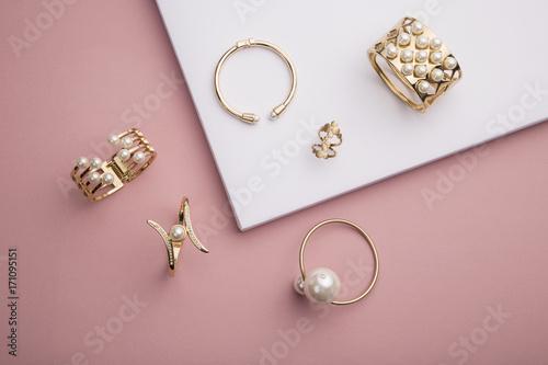 Perłowe złote bransoletki i pierścionek na różowym i białym tle