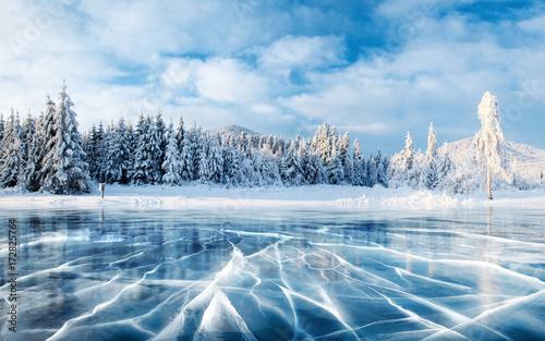 Niebieski lód i pęknięcia na powierzchni lodu. Zamarznięty jezioro pod niebieskim niebem w zimie. Wzgórza sosen. Zimowy. Karpackie, Ukraina, Europa.