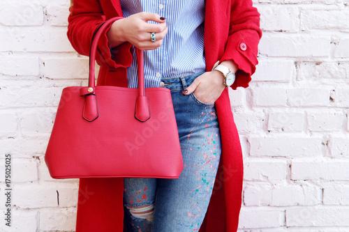 Moda jesień strój kobieta w czerwonym płaszczu ze skórzaną torbą